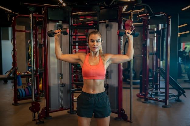 Jonge vrouw die met domoren uitoefenen om bicepsen en schouders in gymnastiek te versterken