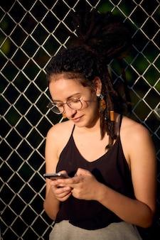 Jonge vrouw die met dreadlocks een sms-bericht schrijft op haar mobiel.
