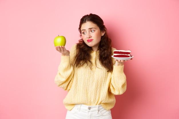 Jonge vrouw die met droevig en teleurgesteld gezicht kijkt naar groene appel terwijl ze een stuk heerlijke cake in een andere houdt, wil een dessert eten, staande tegen een roze muur.