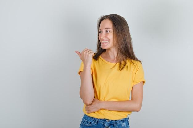 Jonge vrouw die met duim naar kant wijst en in t-shirt glimlacht