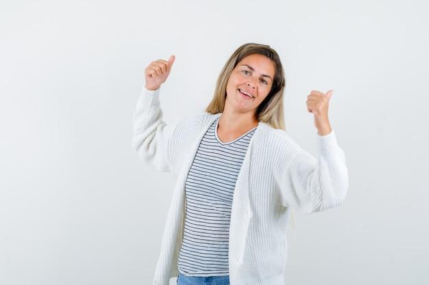 Jonge vrouw die met duimen in t-shirt, jasje terug richt en gelukkig kijkt. vooraanzicht.