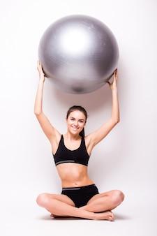 Jonge vrouw die met een bal uitwerkt die op een witte muur wordt geïsoleerd