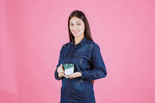 Jonge vrouw die met een koffiekop en positief glimlacht voelt