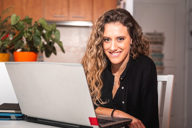 Jonge vrouw die met een laptoop werkt