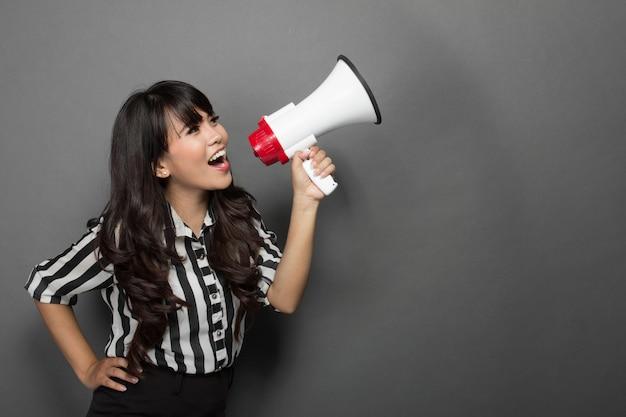 Jonge vrouw die met een megafoon schreeuwt