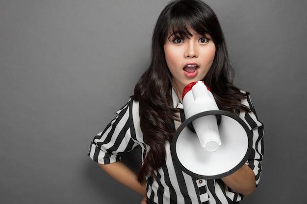 Jonge vrouw die met een megafoon tegen grijze achtergrond schreeuwt