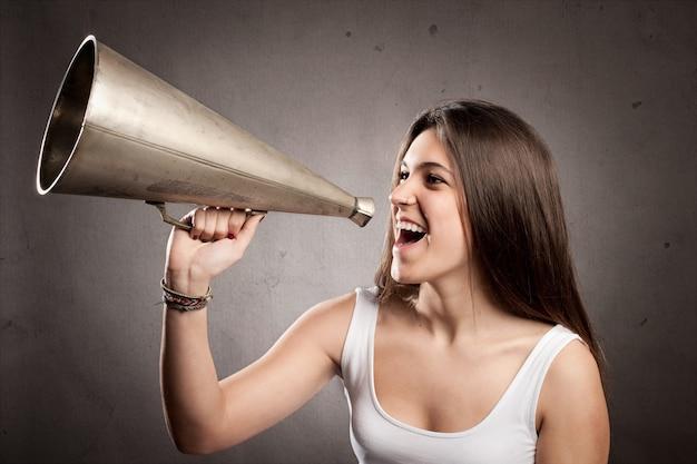 Jonge vrouw die met een oude megafoon schreeuwt