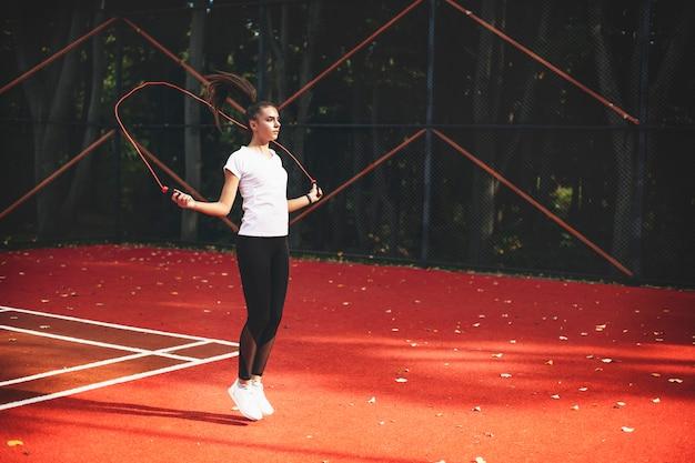 Jonge vrouw die met een springtouw buiten in een sportpark in de ochtend springt.