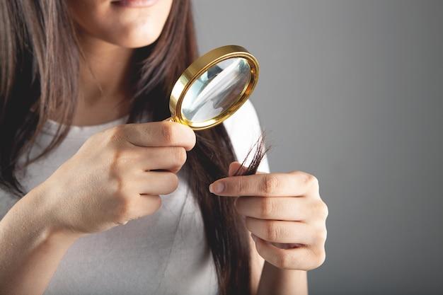 Jonge vrouw die met een vergrootglas naar haar haar kijkt