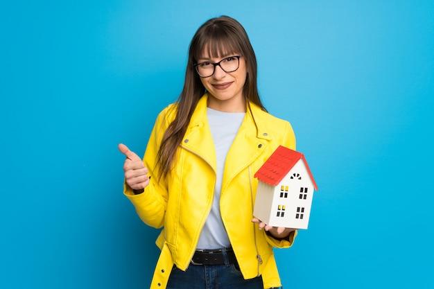 Jonge vrouw die met geel jasje op blauwe muur een klein huis houdt