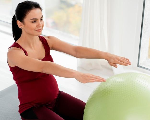 Jonge vrouw die met geschiktheidsbal uitoefent terwijl zij zwanger is