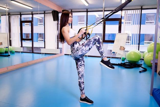 Jonge vrouw die met geschiktheidsriemen uitoefent in de gymnastiek.