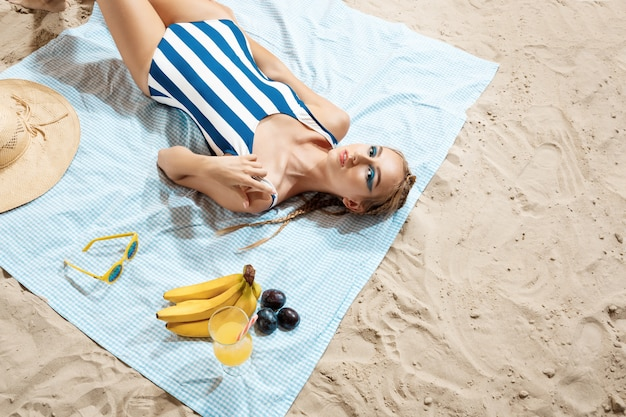 Jonge vrouw die met gestreepte swimwear zonnebaadt