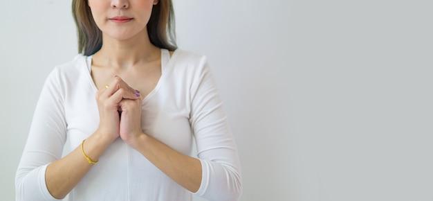 Jonge vrouw die met gevouwen hand bidt.