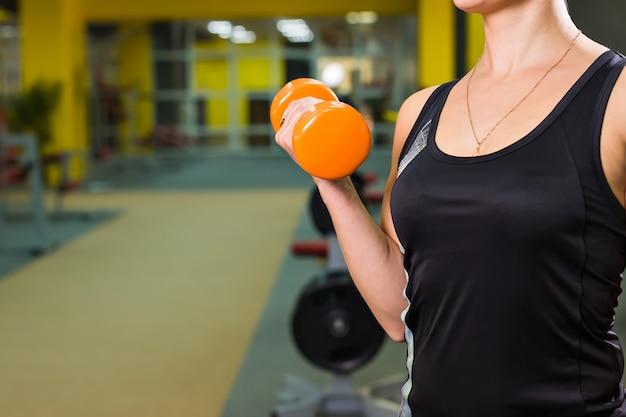Jonge vrouw die met gewichten in de gymnastiek uitoefent