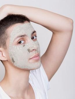 Jonge vrouw die met gezichtsmasker de camera bekijkt