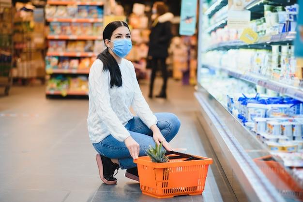 Jonge vrouw die met gezichtsmasker door kruidenierswinkelopslag loopt