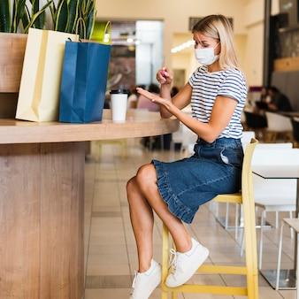 Jonge vrouw die met gezichtsmasker handen desinfecteert