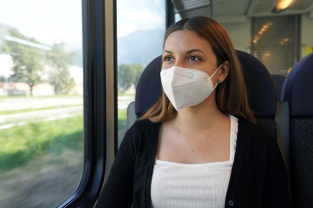 Jonge vrouw die met gezichtsmasker kn95 ffp2 door treinvenster kijkt