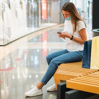 Jonge vrouw die met gezichtsmasker mobiele telefoon controleert