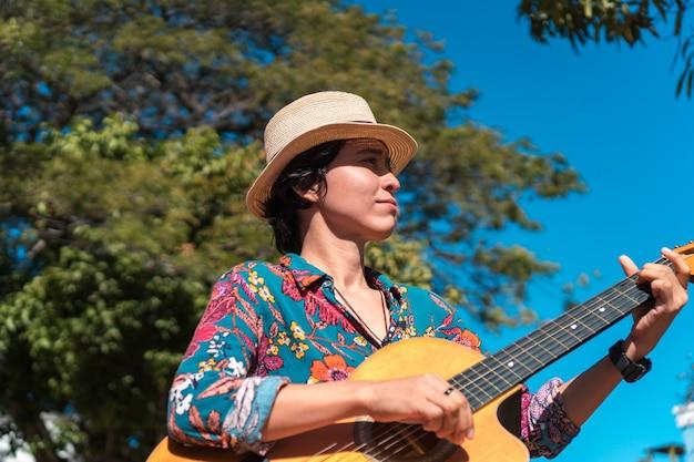 Jonge vrouw die met gitaarkoffer omhoog kijkt