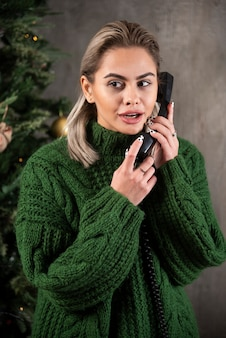 Jonge vrouw die met groene sweater een gesprek met de mobiele telefoon houdt