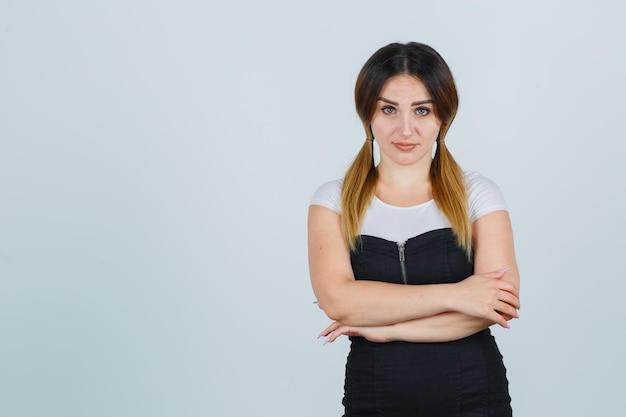 Jonge vrouw die met haar armen over elkaar staat en er zelfverzekerd uitziet