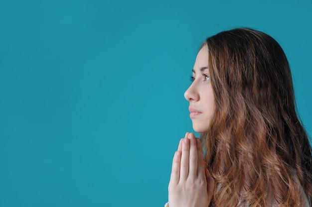 Jonge vrouw die met haar gevouwen handen bidt