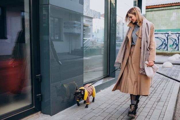 Jonge vrouw die met haar hond franse buldog winkelt