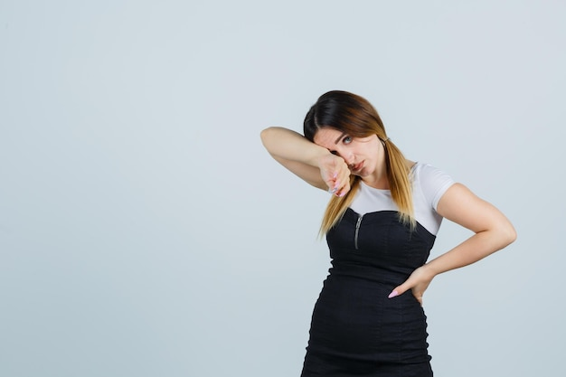 Jonge vrouw die met haar hoofd op de elleboog leunt en er uitgeput uitziet