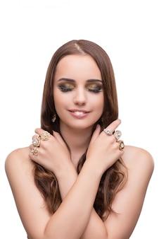 Jonge vrouw die met haar juwelen pronkt die op wit worden geïsoleerd