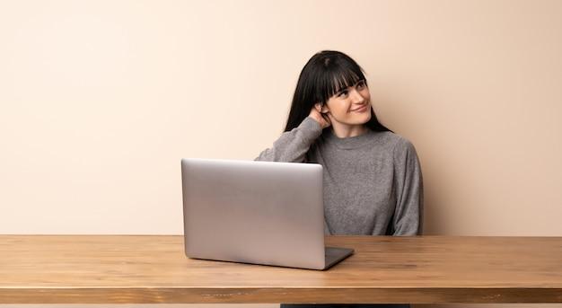 Jonge vrouw die met haar laptop werkt die een idee denkt terwijl het krassen van hoofd
