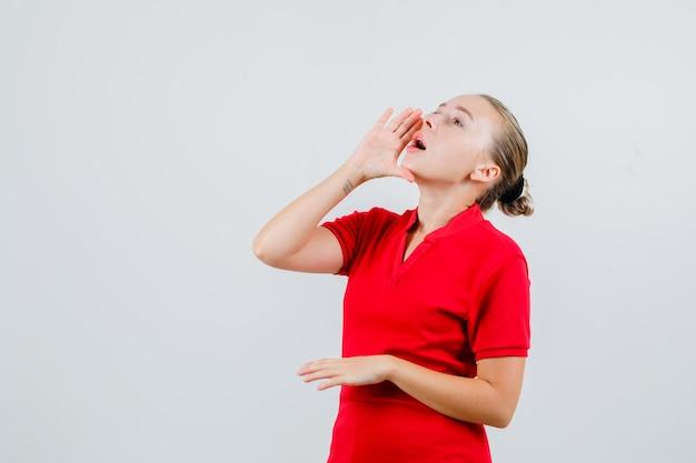 Jonge vrouw die met hand dichtbij mond in rood t-shirt schreeuwt