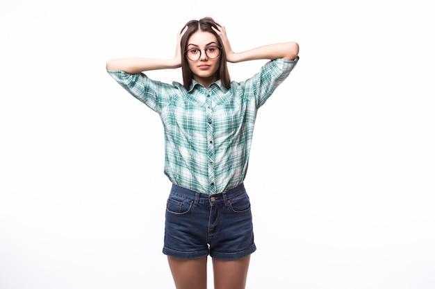 Jonge vrouw die met handen haar oren bedekt, over wit