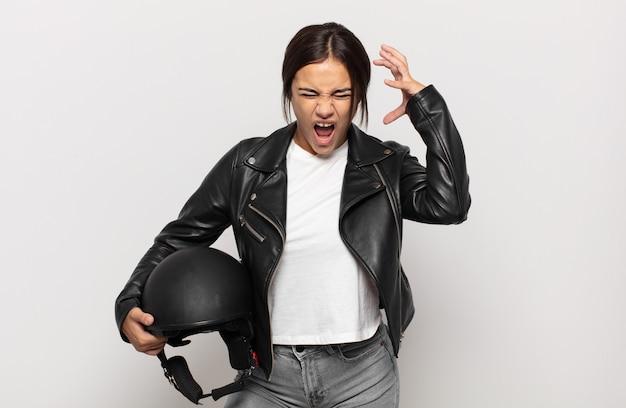 Jonge vrouw die met handen in de lucht gilt, zich woedend, gefrustreerd, gestrest en boos voelt