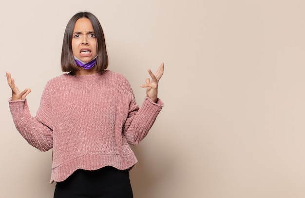 Jonge vrouw die met handen in de lucht schreeuwt, zich woedend, gefrustreerd, gestrest en boos voelt