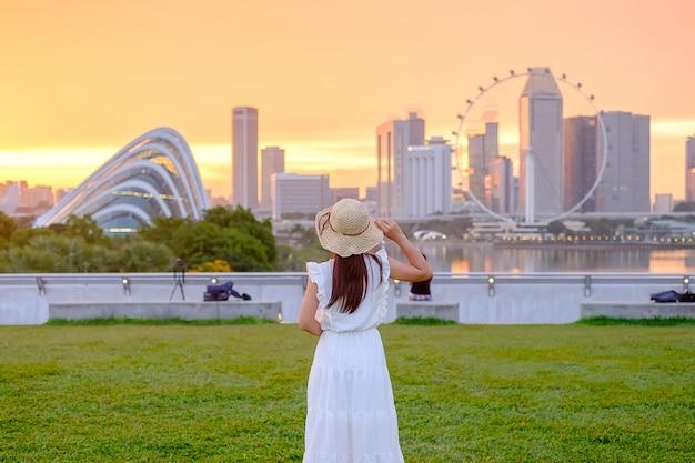 Jonge vrouw die met hoed bij zonsondergang, gelukkig aziatisch reizigersbezoek reist in stad de van de binnenstad van singapore. oriëntatiepunt en populair voor toeristenaantrekkelijkheden. azië reizen concept