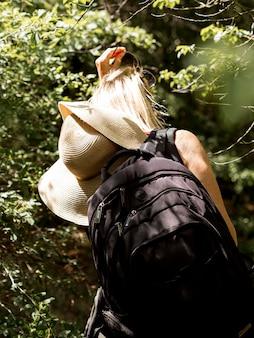 Jonge vrouw die met hoed bos onderzoekt
