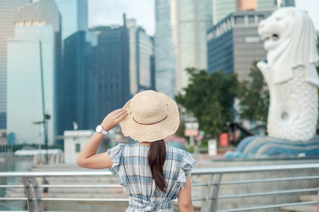 Jonge vrouw die met hoed in de ochtend reist, gelukkig aziatisch reizigersbezoek in de stad van singapore de stad in. oriëntatiepunt en populair voor toeristenaantrekkelijkheden. azië reizen concept