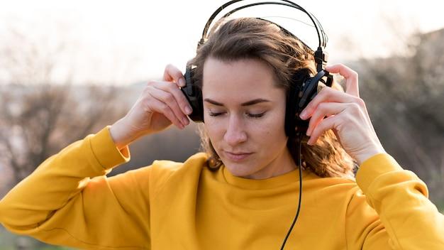 Jonge vrouw die met hoofdtelefoons aan muziek luistert