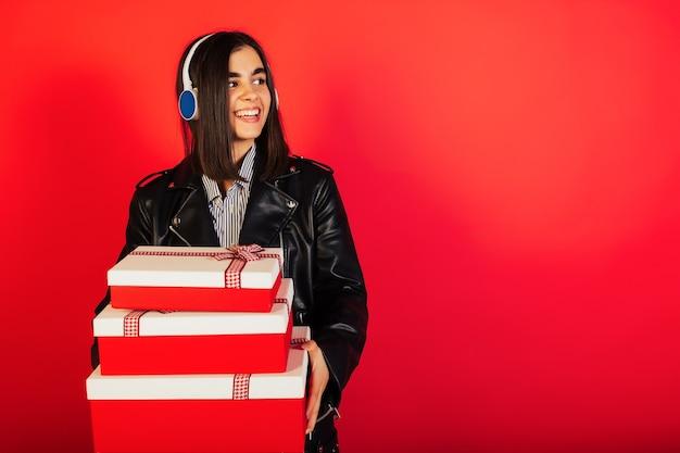 Jonge vrouw die met hoofdtelefoons een rode giftdozen houdt die op een rode muur worden geïsoleerd