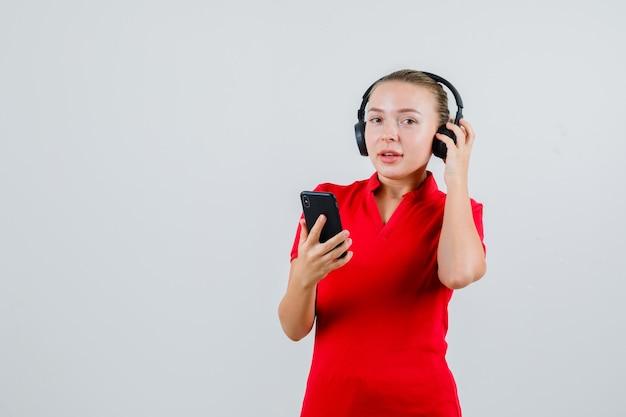 Jonge vrouw die met hoofdtelefoons op mobiele telefoon in rood t-shirt luistert en positief kijkt