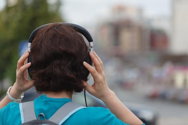 Jonge vrouw die met hoofdtelefoons van tijd in een stad geniet.