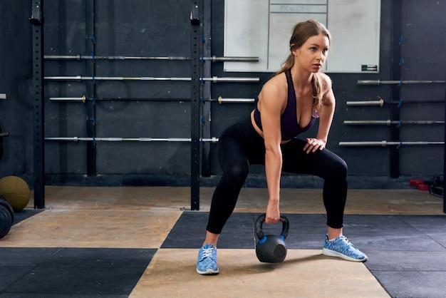Jonge vrouw die met kettlebells in gymnastiek hurken