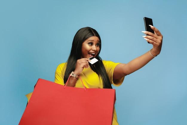 Jonge vrouw die met kleurrijke pakken op blauwe muur winkelt