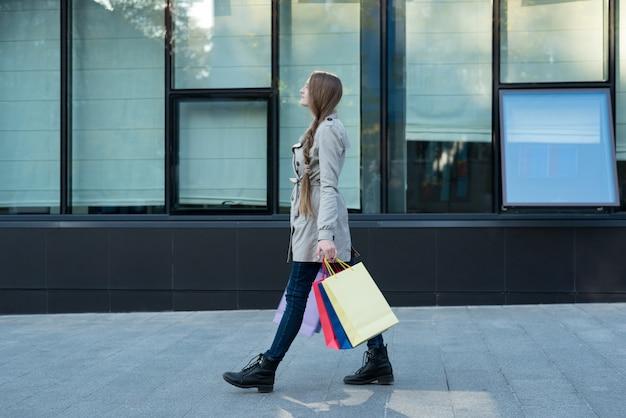 Jonge vrouw die met kleurrijke zakken op de straat loopt.