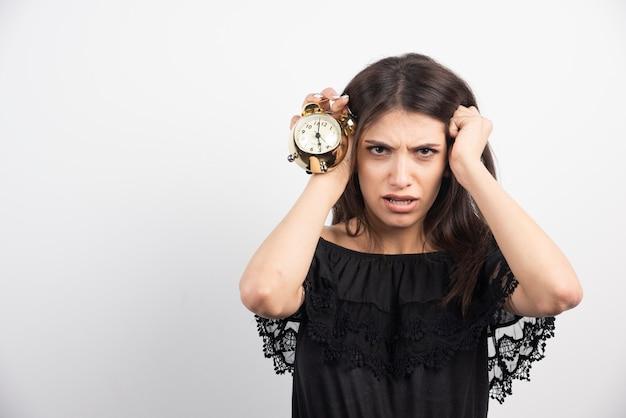 Jonge vrouw die met klok haar hoofd houdt.
