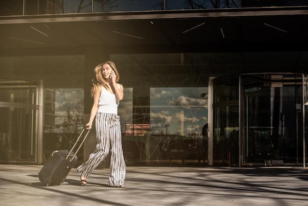 Jonge vrouw die met koffer op de straat loopt die telefoon met behulp van