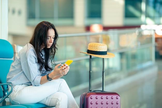 Jonge vrouw die met koffie in een luchthavenzitkamer op vluchtvliegtuigen wacht
