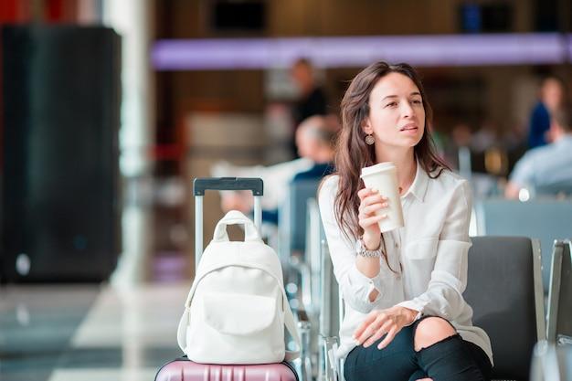 Jonge vrouw die met koffie in een luchthavenzitkamer op vluchtvliegtuigen wacht.
